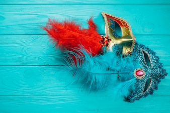 Due maschere di Carnevale veneziano rosso e blu sulla tavola di legno blu