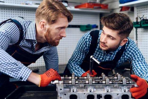 Due meccanici stanno in piedi e guardano la parte con un guasto.
