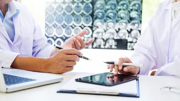 Due medici analizzano una scansione o un film a raggi x o spiega una scansione tc