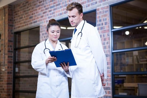 Due medici che esaminano lavagna per appunti e che discutono vicino alla biblioteca nell'ospedale