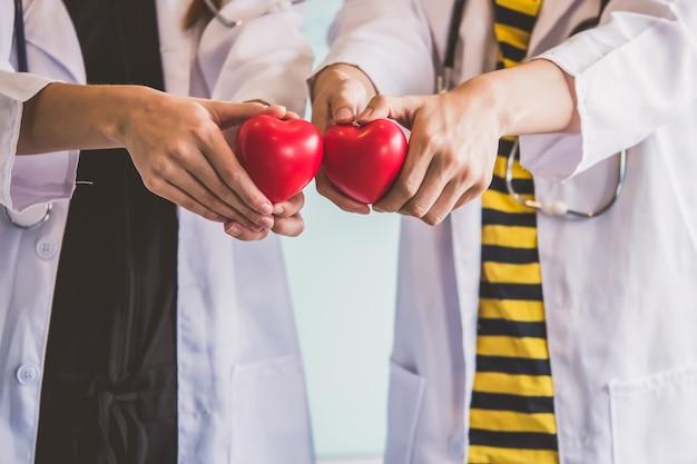 Due medici che tengono cuore rosso, concetto di assistenza sanitaria.