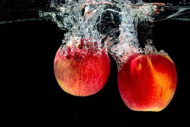 Due mele rosse che spruzzano nell'acqua