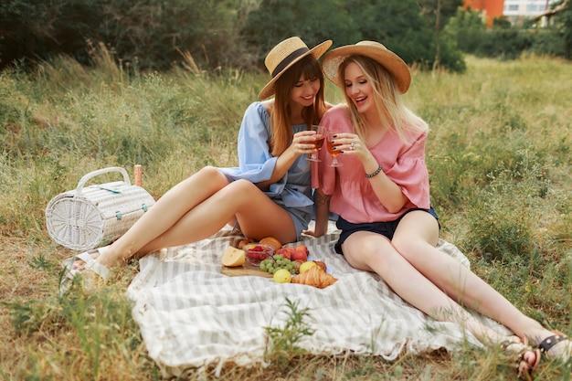 Due meravigliose ragazze in cappello di paglia che trascorrono le vacanze in campagna, bevendo spumante.