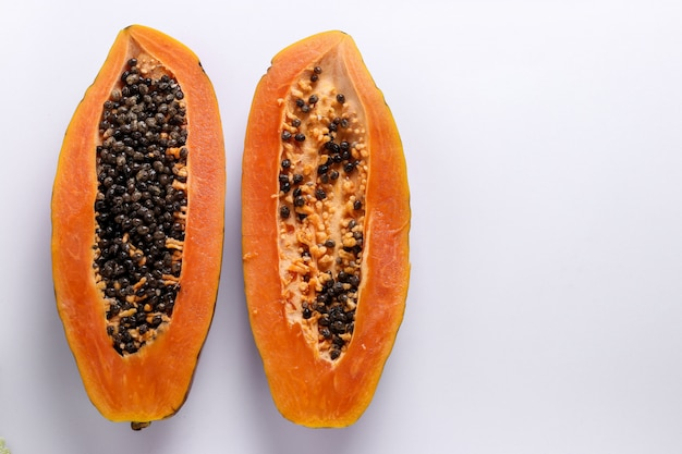 Due metà di papaia matura su superficie bianca, orientamento orizzontale, spazio di copia