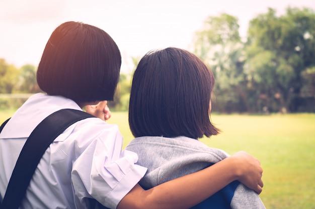Due migliori amiche che pensano e si abbracciano con amore