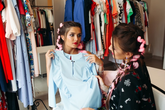 Due migliori amiche per lo shopping, facendo scegliere e guardando il vestito blu.