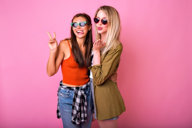 Due migliori amiche positive divertendosi indossando occhiali da sole