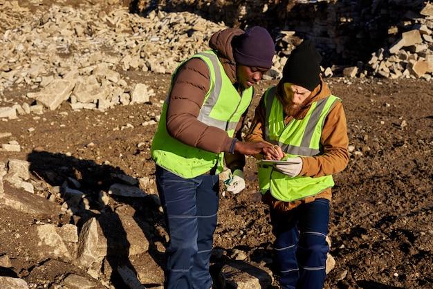 Due minatori d'oro che ispezionano la terra