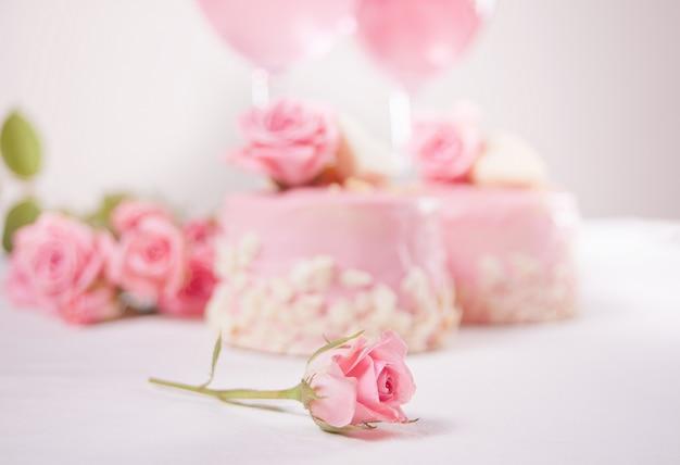 Due mini torte, bicchieri di vino d'uva rosa e fiori di rosa su un tavolo bianco. concetto di cena romantica. concentrati su una piccola rosa.