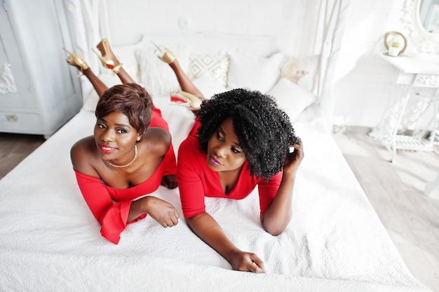 Due modelli afroamericani di moda in abito rosso di bellezza e tacchi alti dorati, womans sexy in posa abito da sera si trovano sul letto.