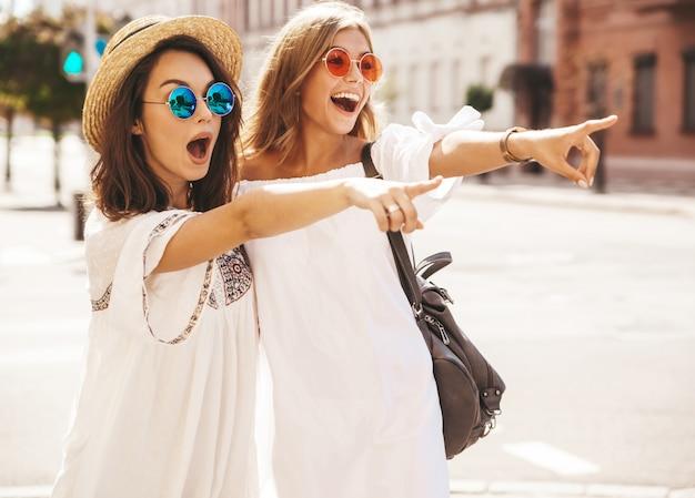 Due modelli di donne castane e bionde del giovane hippy alla moda di modo nel giorno soleggiato di estate nella posa bianca dei vestiti dei pantaloni a vita bassa. indicando sulle vendite del negozio