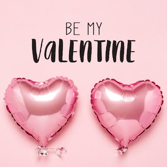 Due mongolfiere rosa a forma di cuore su una superficie rosa. concetto di san valentino