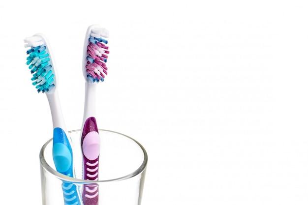 Due nuovi spazzolini da denti in vetro isolato su uno sfondo bianco