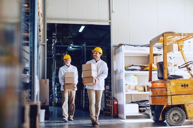 Due operai in divisa bianca e con elmetti gialli sulle teste trasferiscono scatole pesanti in magazzino.