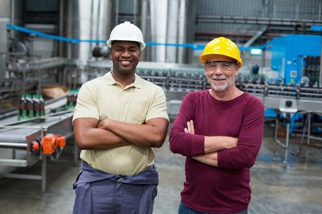 Due operai in piedi con le braccia incrociate nell'impianto di produzione di bevande