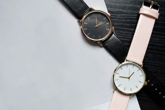 Due orologi di colore nero e rosa, senza numeri su un tavolo nero. carta leggera, posto per il tuo testo