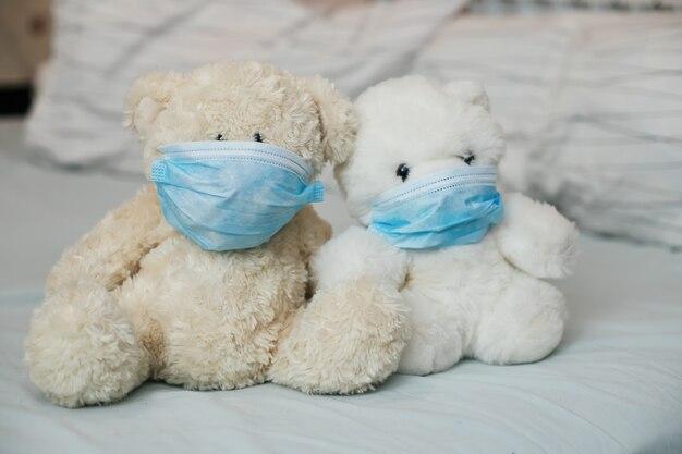Due orsi giocattolo con maschere mediche sul letto. malattia di malattia nei bambini. coronovirus, quarantena, epidemia, pandemia, raffreddore, malattia. concetto di medicina e salute.