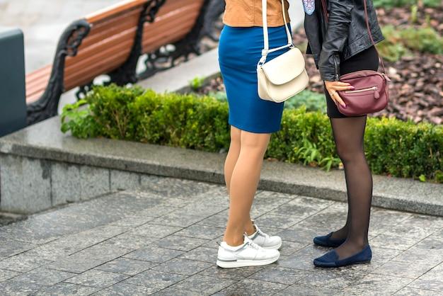 Due paia di gambe sottili per ragazze in gonne corte, sneakers in pelle bianca e comode scarpe estive su piattaforma bassa. moda, stile e design moderno.