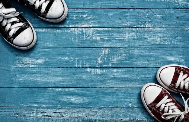 Due paia di scarpe da ginnastica su sfondo blu vintage