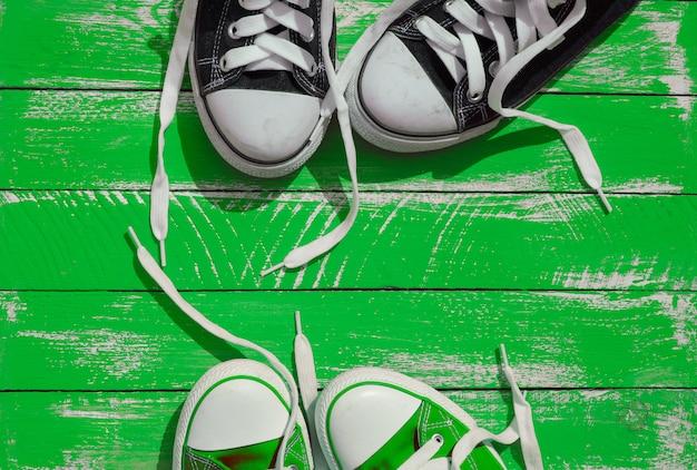 Due paia di sneakers giovanili con lacci slacciati sulla superficie verde