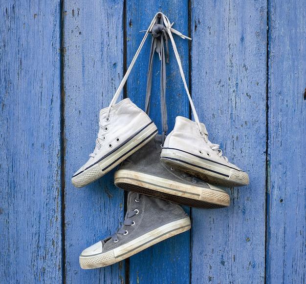 Due paia di vecchie scarpe da ginnastica in tessuto appese a un chiodo