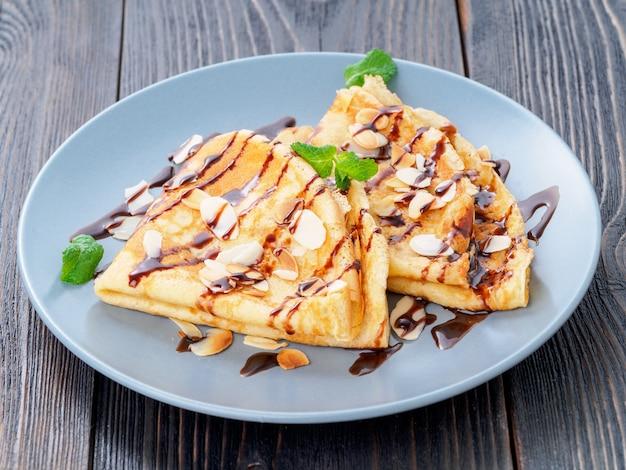 Due pancake con sciroppo di cioccolato, scaglie di mandorle sul piatto
