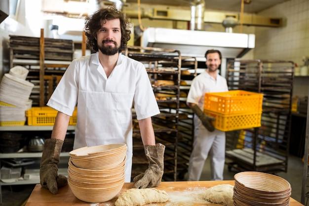 Due panettieri sorridenti che lavorano in cucina prodotti da forno