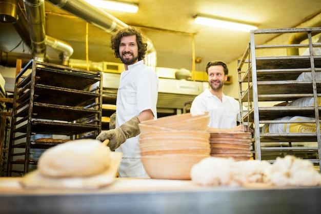 Due panettieri sorridenti che preparano il pane in cucina prodotti da forno