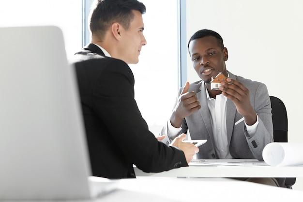 Due partner commerciali che si incontrano in ufficio: uomo africano in abito grigio che tiene casa modello in scala, spiegando i dettagli del suo design esterno, seduto con il suo collega alla scrivania con rotoli di cianografia