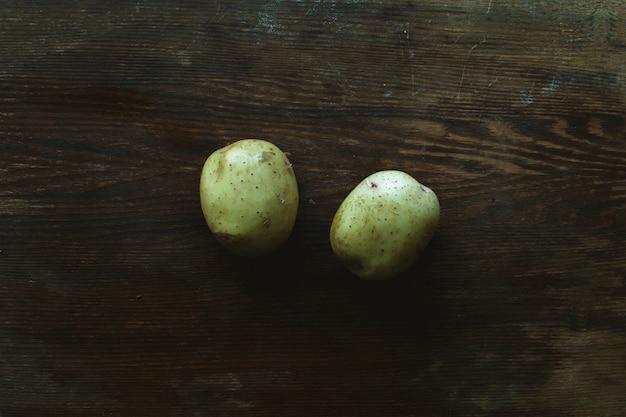 Due patate fresche su legno