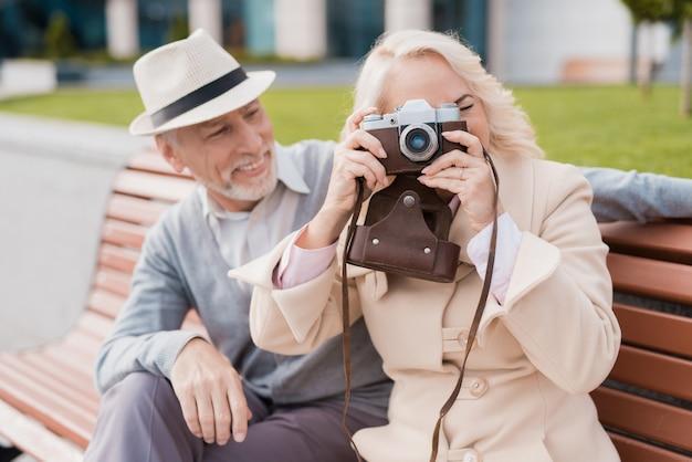 Due pensionati scattano foto su una vecchia macchina da presa