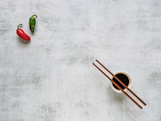 Due peperoncini e salsa di soia con le bacchette. sfondo di cibo.