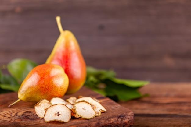 Due pere rosse fresche con i chip secchi su fondo di legno