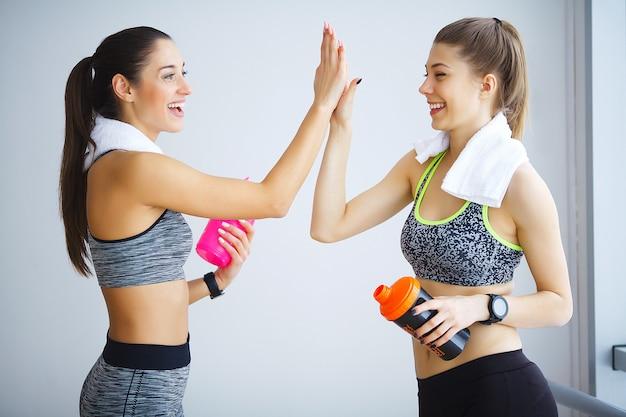 Due persone che amano il fitness sono in piedi da una parte in posizione e si tengono con un'altra mano con un sorriso. è una scena bella e adorabile.