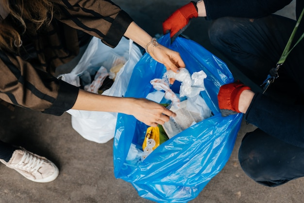 Due persone che smistano i rifiuti. concetto di riciclaggio. zero sprechi