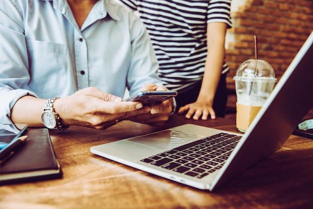 Due persone che utilizzano il cellulare mentre si incontrano in un negozio di caffè per lavoro proprietario di pmi