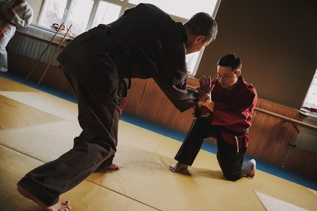 Due persone combattenti di arti marziali in kimono nero e rosso.