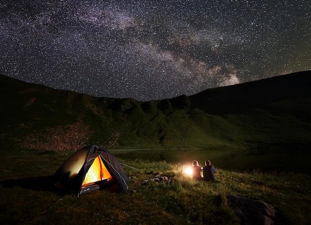 Due persone di notte in campeggio in montagna vicino al lago sotto il cielo cosparso di stelle e luminosa via lattea