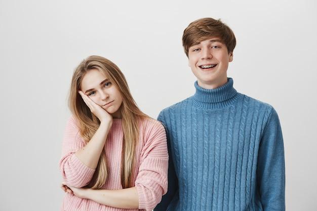 Due persone in piedi, la ragazza si sente annoiata mentre il ragazzo sorride allegro