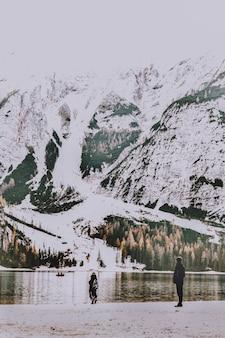 Due persone in piedi sulla riva che si affaccia sullo specchio d'acqua e montagna innevata