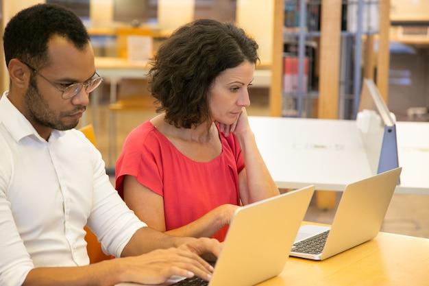 Due persone riflessive, seduto con i computer portatili in biblioteca