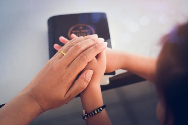 Due persone si tengono per mano e pregano insieme