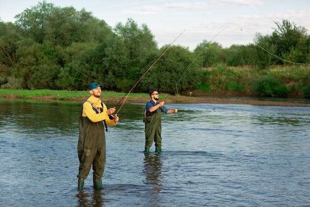 Due pescatori sono in piedi nel fiume con stivali di gomma