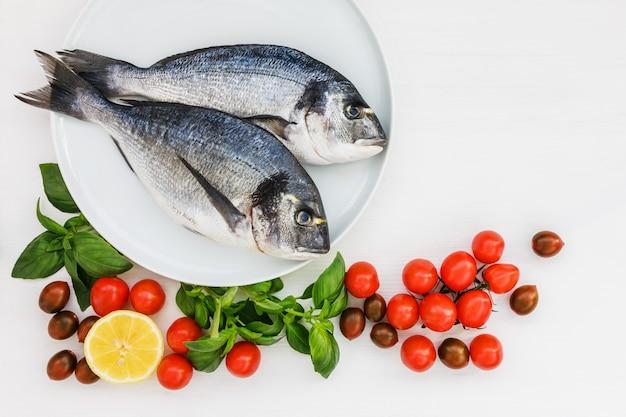 Due pesci dorado crudo sul piatto bianco con verdure.