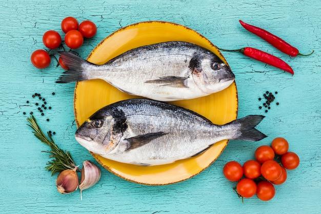 Due pesci dorado freschi sul piatto giallo e verdure sul tavolo blu. vista dall'alto.