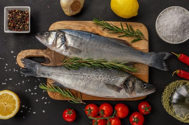 Due pesci freschi della spigola con rosmarino e le verdure sulla tavola nera