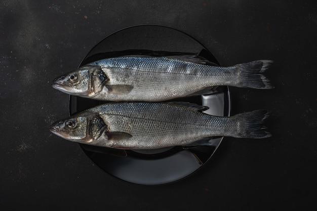 Due pesci freschi della spigola su una banda nera