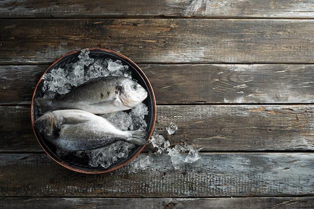 Due pesci freschi di dorado in ghiaccio chip sul vassoio tondo vintage
