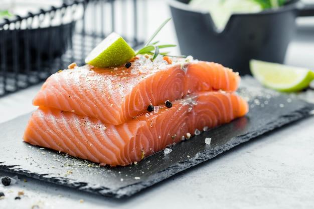 Due pezzi di filetto di salmone crudo con erbe fresche rosmarino, spezie e olio d'oliva su lastra di ardesia nera