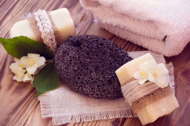 Due pezzi di sapone secco con un gelsomino, un asciugamano e una pietra pomice